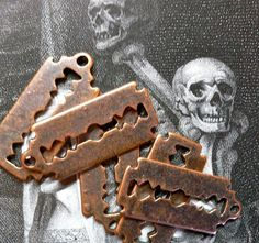 Miniature RAZOR BLADE CHARMS with an aged look!    Interesting that the reverse side had to be imprinted with the words razor blade. The look on the characters face in the photo is similar to the look that I had when I discovered that.    Nevertheless, cute and charming!    COLOR: distressed faux copper  MEASUREMENTS: app 22x9mm with loop  CONDITION: new    FIVE CHARMS