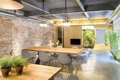 salle à manger scandinave avec table en bois, chaises Eames et revêtement de sol en béton ciré