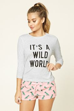 "A PJ set featuring a knit tee with a ""It's A Wild World"" graphic on the front, 3/4 sleeves, and a round neckline, as well as a pair of woven shorts with an allover dinosaur print and an elasticized drawstring waist."