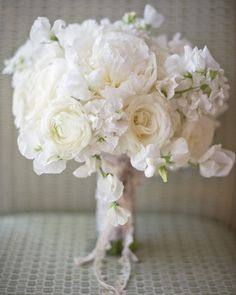 A vision in white: Peonies, sweetpeas, stock, garden roses, ranunculus, and dusty miller wrapped with lace and pinned with a vintage brooch