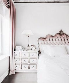 Lovely white and pink bedroom with crisp sheets and an antique pink and gold headboard.