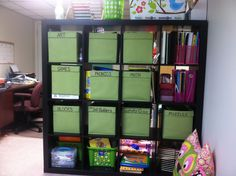 Homeschool Room Organization: IKEA Bookcase with fabric bins (from Bed, Bath and Beyond).  The bottom shelves are things my toddlers may play with.  The top right cubby is Lesson Plans and Teacher Books.  The shelf under it has each of the girls' textbooks in their own pink file box.