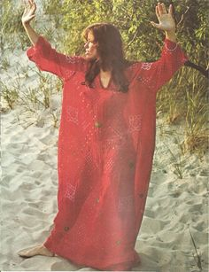 Carly Simon wearing red caftan standing on the sand. Photo from CIRCUS magazine, March 1973.