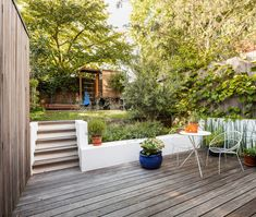 Decking, outdoor furniture, white wire chairs, small white table, garden bed, planter box, white rendered concrete, ivy wall