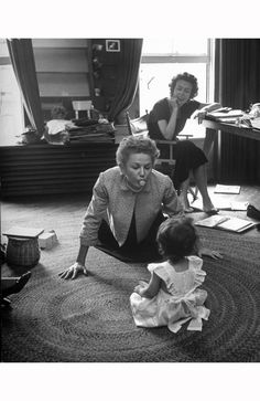 Eileen Ford conducting her job of running the ford model agency while model Jone Pedersen entertains fords daughter 1948 nina leen