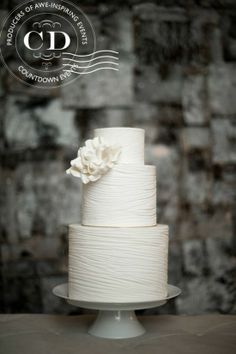 simple & elegant white 3 tier wedding cake with a gorgeous bloom