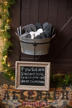 """I wanted an option for ladies & men to kick off their shoes. I bought a whole bunch of flip flops in different sizes from Old Navy off season so they were super cheap and put them in a drink tub I had. """"If your feet are tired and sore, grab a pair and dance some more."""""""