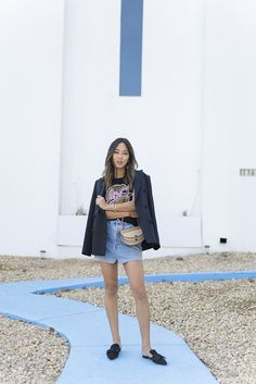 Aimee Song from the blog Song of Style shares her day-to-day outfit. Wearing a Vetements denim skirt, Loewe t-shirt, and Prada mule slides
