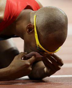 The Dominican Republic's Felix Sanchez kisses a family photograph after his gold medal win in the men's 400-meter hurdles.