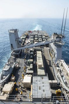 A working party, consisting of Sailors and Marines, moves supplies from the flight deck of the dock landing ship USS Harpers Ferry (LSD 49) to the interior of the ship during a vertical replenishment with the military sealift command ship USNS Cesar Chavez (T-AKE 14).