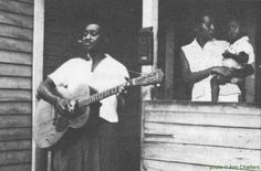 """Baby Tate with his wife and son, Spartanburg, South Carolina, 1962; source: Front cover of Asch LP A-101 (US 1967) """"The Blues - Music from the Documentary Film by Samuel Charters""""; photographer: Ann Charters; the guitar is a 1950s """"Orpheum Leader"""", manufactured by Kay"""