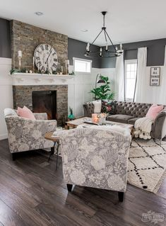Beautiful traditional living room with modern accents - grey velvet sofa, patterned chairs, shag rug, board & batten, charcoal black paint, rustic fireplace