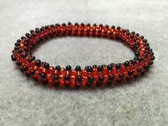 Ladybird spots red and black bangle.  This beautiful beaded bangle just slips over your hand.  Also available made to order in other colours and
