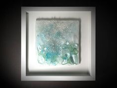 Title: Effervesce ~ 3 (2017) Of the Sea Stratum series at maywaynorth.com The listing is for a custom fused glass sculpture very similar to the one pictured; 6-8 week production time. Choose a 12 x 12 (shown) frame or 14 × 14 frame; the sculpture is between 7 - 8 inches free form square and increases in size slightly with a larger frame. Description ~ In the deepest parts of the ocean, at temperatures of 380° C, geothermal vents in the sea floor create hot springs - a fascinating show of…