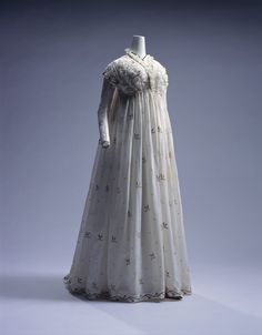 Dress (round gown)c. 1795-Italy  White muslin one-piece dress with long train; blue and brown cotton and silver embroidery of plant patterns; shirring at top of front; lace decoration around neckline.