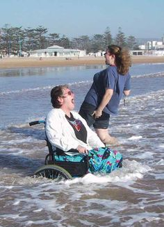 Holidays for All ~ a consortium of accessible holiday providers working in partnership to broaden your horizons   Lady wheelchair user and friend enjoy the sea