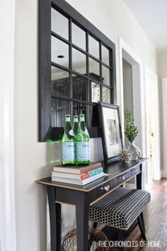 A simple vignette for the kitchen with a narrow console and windowpane mirror