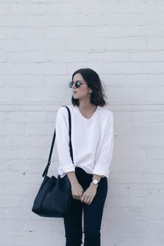Blogger Take Aim wears a white sweater, black skinny jeans, bucket bag, and round sunglasses