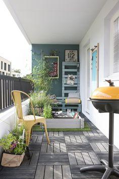 Prenez exemple sur cette composition car elle a tout bon | La nature est présente à travers les touches de verdure des jardinières, du sol en bois naturel, du tapis en faux gazon et d'un pan de mur vert. | Les éléments jaunes contrastent avec le vert et le réveillent en distillant leur effet bonne humeur. | La déco n'est pas en reste : le balcon, traité comme un espace de transition dedans/dehors, s'empare de tableaux et d'étagères qui mime l'aménagement intérieur