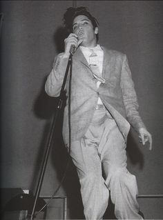 """Elvis Presley performing live on stage at the Pan-Pacific Auditorium in Los Angeles, CA on Tuesday, October 29, 1957. The cops were filming Elvis's performance that night. """"They came out to film Elvis because they said he was too wild and that's the night that Elvis just wiggled his fingers when he sung 'Hound Dog'...You couldn't even hear Elvis. The girls screamed through the whole concert..."""" ~ Glen Glenn, American rockabilly singer 
