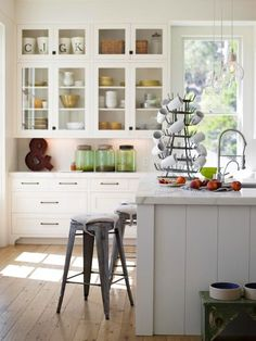 An all white kitchen broken up with glass fronted cabinets, large accessories on the counter tops and a couple of urban hardware stools