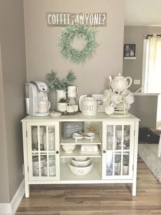 Crushing on this gorgeous coffee bar. Loving the all white theme. Love the Rae and Dunn canisters. Love the teapot with the teacups and the open feel of the bottom. So gorg! #farmhouse #coffeebar #raeanddunn