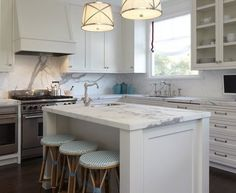 A honed marble island provides additional work surface and seating.