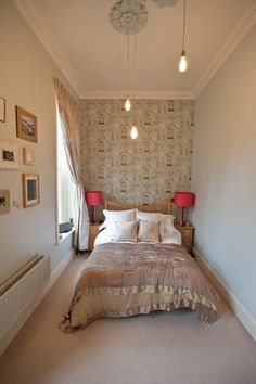 7. Detract with a feature wall. In a narrow room, bring the far wall forward with fabulous wallpaper. This pretty design links the pale blue walls and bronze quilt for a room that feels cohesive and has bags of personality.