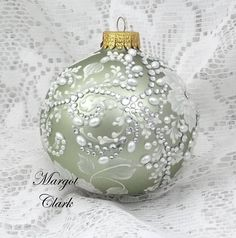 Soft green glass ornament with lots of white textured painted roses all over, accented with pearls and rhinestones. Measures 3 x 3 1/2. Gift boxed.