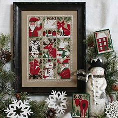 Prairie Schooler Evergreen - Cross Stitch Pattern. Model stitched on 32 Ct. Sage Jobelan with DMC floss. Stitch Count: 155H x 107W. Ornaments have a stitch coun