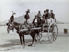 Portrait of a family or a group of people on a typical painted sicilian cart with the horse caparisoned with plumes, ribbons and bells. The people are sitting on chairs set on the wagon