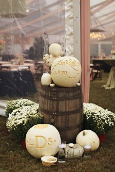 Monogram carved white pumpkins, wine barrel, and white mums at the tent entrance for a fall wedding.  Outdoor North Carolina southern farm wedding.