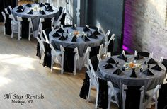 A classic black and white wedding combo. White linens with a black sparkle overlay, black napkins, and black chair ties. Simple white wood folding chairs complete the look.