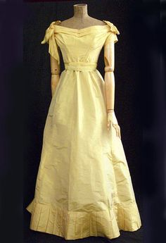 Silk taffeta ball gown, c.1870  This lovely ball gown is fashioned from unfaded gold taffeta. The color is as fresh and glowing today as when worn by the owner to her first ball. What a wonderful period piece!  The hand-sewn bodice features a wide neckline, shoulder bows, and short pleated sleeves. The bodice is boned and lined with ivory-polished cotton. The sleeves are set in with narrow piping, and the bodice hem is finished corded piping. The bodice closes in back with hooks.  The…