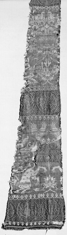 Brocade 14th century, 47 x 63 cm, The ground is grayish blue silk. The design arranged in horizontal bands is woven with white and pinkish red silk, and linen thread wound with very much tarnished gilded gold beaters skin. In the wider bands are palmettes, hunting leopards, dogs and birds. In the narrower bands are animals, rosettes, and Arabic letters, in circles.