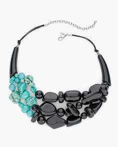 A flash of faux turquoise lightens up the drama of this lavish noir necklace.    Plastic, synthetic, howlite and metal.  Imported.