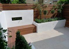 Witte tuinafscheiding met uitsparing gecombineerd met teakhouten vlonder en zitbank