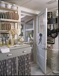 Love the curtained cabinets.... It's soft, colorful, country, homey....