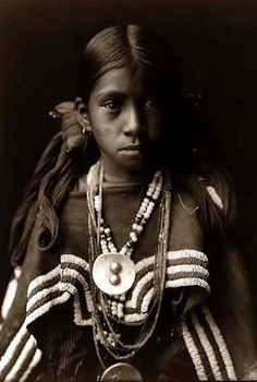 Jicarilla Apache Indian girl wearing a dress with a buckskin cape, necklaces and medallions around her neck. Her hair is tied on each side of her head with large knot of yarn. | Photo taken in 1905 by Edward S. Curtis.