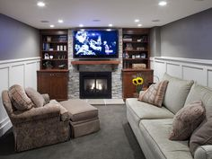 The gas fireplace in this basement living room is flanked by bookcases for storage and display, and full-depth cabinets below house audio/visual equipment. The lights and speakers are connected to the TV so when a movie starts, the lights and fireplace dim, the speakers come alive and go into surround sound and the family is ready. Holy Moly!
