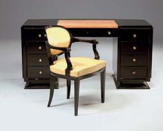 A BLACK LACQUERED WOOD DESK AND AN ARMCHAIR.