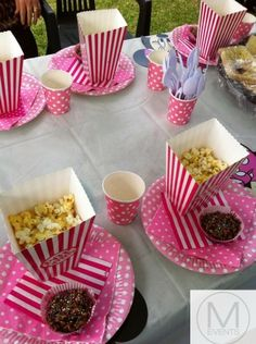 Minnie Mouse table setting. Pink and white polka dot plates,stripe popcorn boxes,strip table napkins and polka dot cups.Great for girls parties or Minnie Mouse fans.