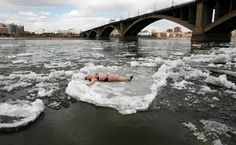 A member of the Cryophil winter swimmers club lies on floating ice from the spring melt on the Yenisei River in the Siberian city of Krasnoyarsk on April 18, 2012. (Ilya Naymushin/Reuters)