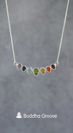 A row of inverted teardrops set with sparkling gemstones imbues this necklace with a thoroughly regal vibe. Facet cut for an extra dazzling effect, each of the gemstones corresponds to a different chakra. From left to right, gemstones include amethyst, iolite, topaz, peridot, citrine, carnelian, and garnet.