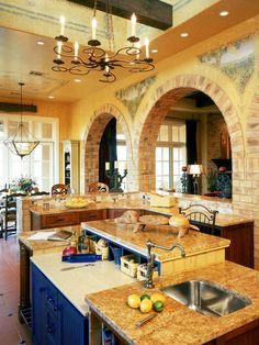 Italian kitchen    The two-tiered marble island in this Italian kitchen has baskets for vegetables and spices, a sink and plenty of room for food prep. Bricked archways painted with Italian frescoes create a grand passage from living room to kitchen. Among the frescoes are handpicked yellow and blue tiles that create a unique patchwork backsplash throughout the space.