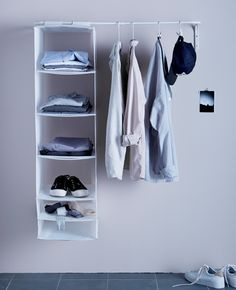 An open clothes rack with shirts hanging from it