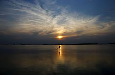 A boy uses a paddle board during sunset on Lake Zicksee in St. Andrae, Austria.