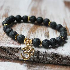 Schwarze Lava Gold OM Armband  Dieses göttliche und klassische Yoga-Armband ist so perfekt für den Alltag.  Informationen: 8mm hochwertigem schwarzen Lavagestein. Starke Latex kostenlose elastische Schnur. Hergestellt in den US-Metall-Komponenten.  Ich benutze nur echten Edelstein, weil nur echten Edelstein die heilende Eigenschaft für Ihre Bedürfnisse hat. Alle Edelsteine sind einzigartig. Bitte erwarten Sie einige Variationen des Steins. Alle sind natürlich schön. Mein Schmuck sind auf…