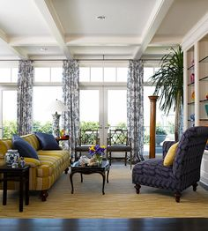 A open and airy sunroom with yellow a gorgeous yellow sofa and rug.