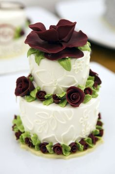 Miniature red roses and white piped flowers give this  individual wedding cake a glamorous touch.